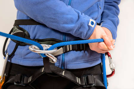 safety harness: Young female rock climber wearing safety harness pulling climbing rope Stock Photo