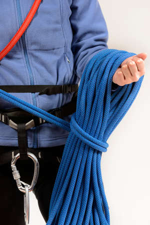 safety harness: Young female rock climber wearing safety harness rolling blue climbing rope on white background Stock Photo