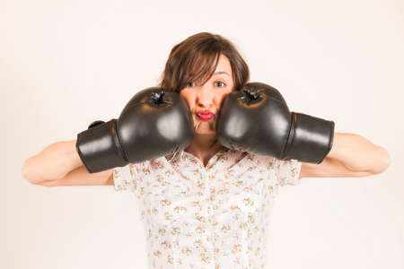knock: Funny young woman wearing boxing gloves and knock down itself, studio shot on white background