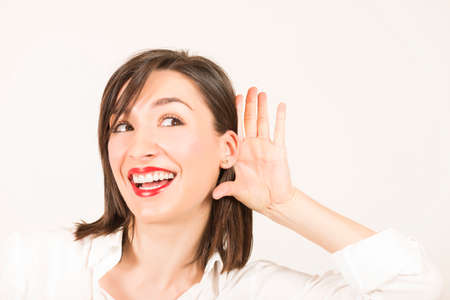 bruit: Young beautiful woman smiling, listening gossip with her hand on an ear, studio shot on white background Stock Photo