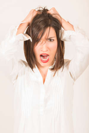 terrorized: Frustrated business woman pulling out her hair not very happy. Terrorized by being late.