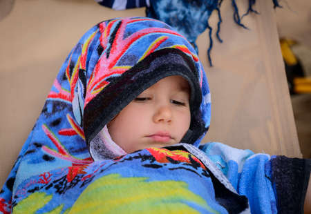 Little girl covered with towel sitting on deckchair after swimming. heatstroke of children, thermic fever. Nap on the beach