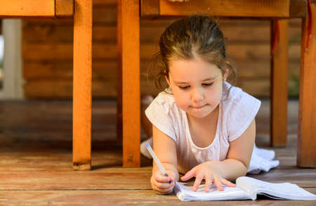 authors: Lovely little girl lying down on the floor drawing on notebook outdoor on backyard terrace. Childhood happiness concept. Stock Photo