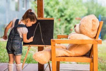 Cute toddler playing teacher role game outdoors. Little child is drawing with pieces of chalk on a blackboard. Happy kid leaning letters and numbers. Children education concept Stock Photo