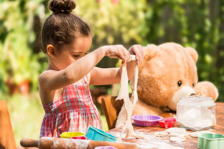 smeary: Happy little chef girl smeary with flour baking and having fun playing with dough teaching her teddy bear how to cook outdoor. Kid playing with dough and teddy bear outdoor in backyard kitchen