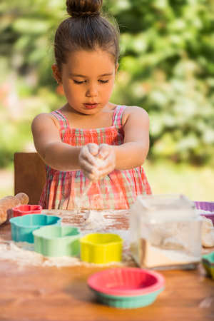 smeary: Happy little chef girl smeary with flour baking and having fun playing with flour outdoor