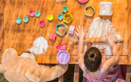 smeary: Happy little chef girl and teddy bear smeary with flour baking and having fun playing with dough outdoor, seen from above. Kid playing with dough and teddy bear outdoor in backyard kitchen Stock Photo