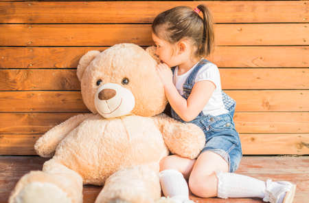Outdoor portrait of expressive little girl whispering to toy bear ear. Little girl playing with teddy bear sharing a secret