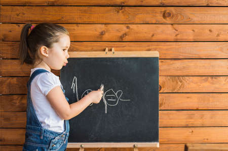 Little child is drawing with pieces of chalk on a blackboard outdoor. Happy kid leaning letters and numbers. Children education concept Stock Photo