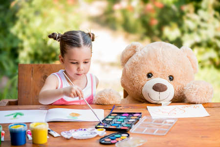 Adorable little girl painting outdoor in a sunny summer day with her teddy bear friend. Outdoor education concept Stock Photo