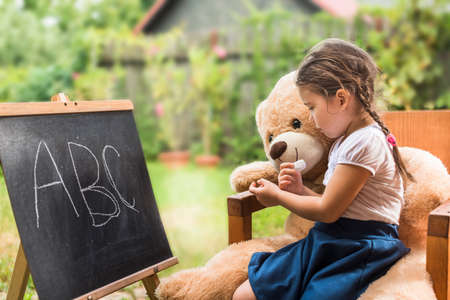 Cute toddler playing teacher role game with her Teddy bear friend outdoors. Happy kid leaning letters Children education concept Stock Photo