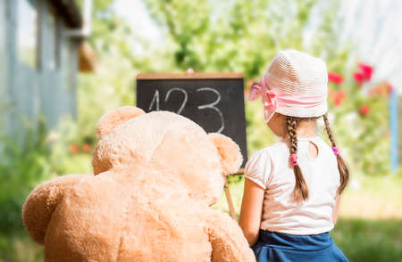 Cute toddler playing teacher role game with her Teddy bear friend outdoors. Happy kid leaning numbers. Children education concept