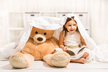 bedtime story: Beautiful little girl reading to her teddy bear toy friend under the blanket Stock Photo