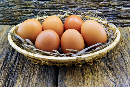continuation: Eggs are placed in a basket on the wooden background.