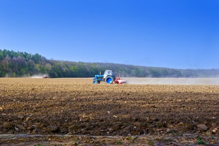 tillage: Tractor for agricultural work in a plowed field.