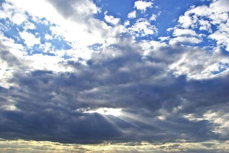 breaking through: Suns rays breaking through the dark rain clouds