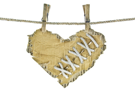 wounded heart: Cardboard heart with lacing on a clothesline.