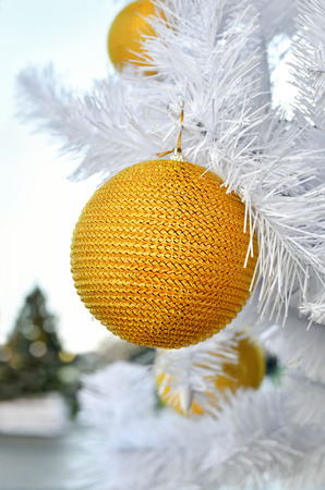 Yellow Christmas toy on a white fluffy tree. Christmas holidays and New Years toys.