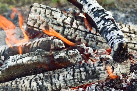 Charred wood burning down in the fire glow, close-up Stock Photo