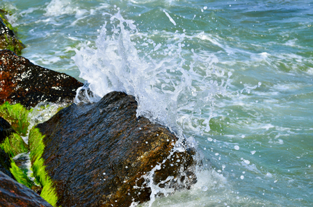 Waves splash on the large boulders on the beach Stock Photo