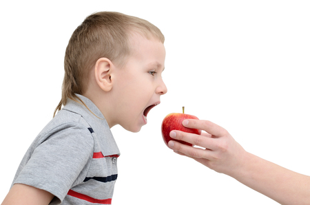 remuneration: Boy eats an apple on a white background