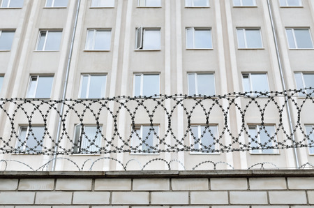 authoritarian: Gray building is fenced with barbed wire. Symbol of  dictatorial and authoritarian regime. Limitation limitation of freedom and human rights. Stock Photo