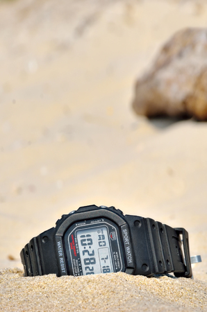 impermeable: Sports waterproof watch forgotten in the sand. Accessories for extreme relaxation.
