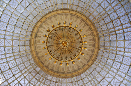 Gold chandelier under a glass dome in the interior