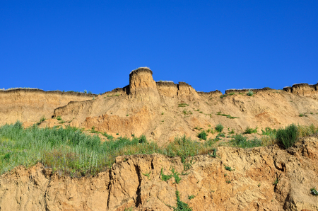 consequence: Deep sandy cliff on the background of blue sky. The destruction of the coast as a consequence of soil erosion. Stock Photo