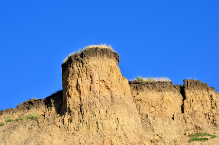 Deep sandy cliff on the background of blue sky. The destruction of the coast as a consequence of soil erosion. Stock Photo