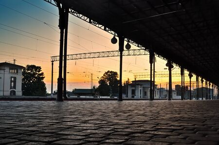 Pavement of paving stones at the railway station, at sunset. Transport infrastructure. Stock Photo