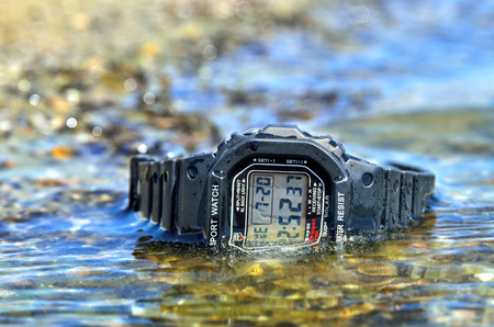 Electronic waterproof watch, immersed in the water stream. Stock Photo