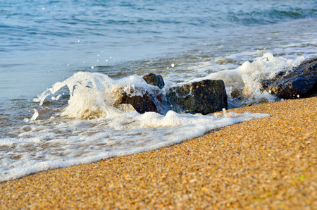 Sea wave washes over stones on the beach