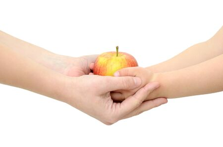 Childrens hands give an apple isolated on white background