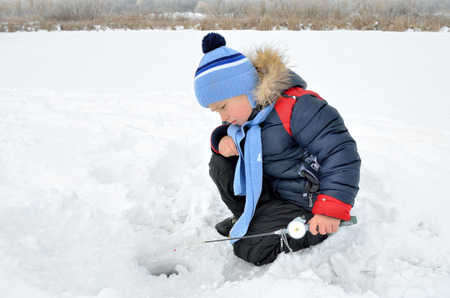 Little boy fishing on the frozen river in winter.