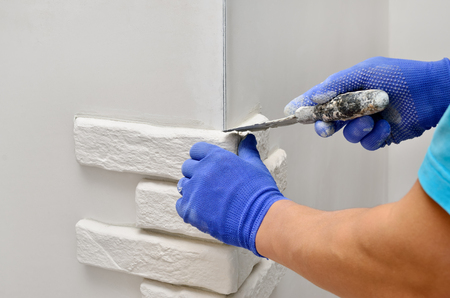 Facing wall decorative tiles, workers in blue glove Stock Photo