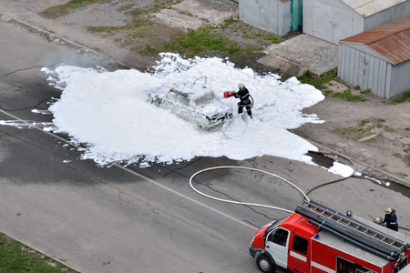 extinguishing: Firefighters are extinguished by a foam burning car. The work of special rescue services.