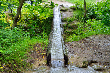 Stream of water flows in wooden gutter in the park