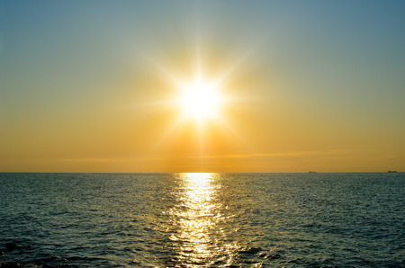 A bright sun over the sea before sunset.