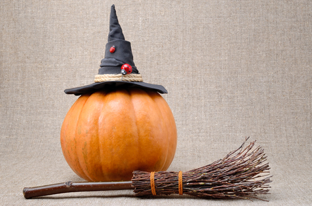 Broom and hat of  witch on a pumpkin for Halloween