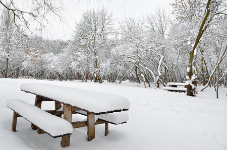 A wooden table in abandoned park on a winter evening