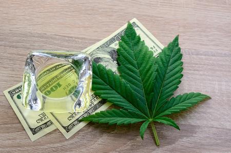Ingresos por la venta de medicamentos de cannabis. Hoja de cannabis, aceite de cáñamo y dinero. Foto de archivo
