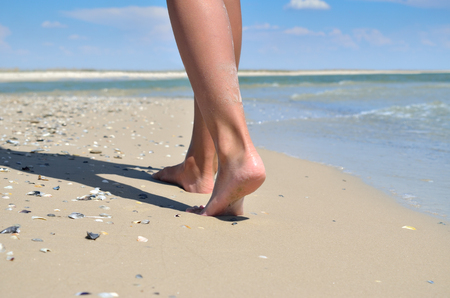 Girl walking barefoot on the sand of the sea beach