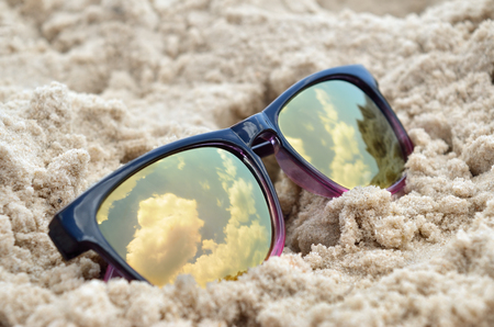 Clouds reflected in sunglasses on the beach