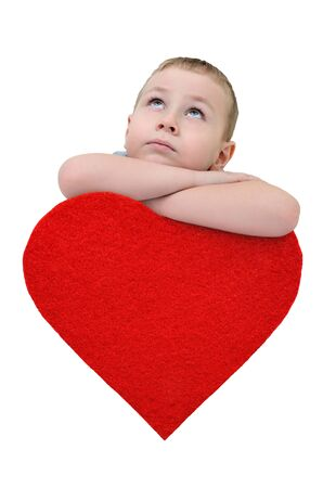 A little boy leaned on a heart and looks up.
