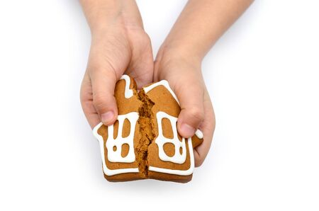 Hands holding house isolated on white background. Concept of a destroyed house in the form of cookies in childrens hands. 写真素材
