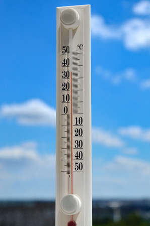 White thermometer against blue sky shows high temperature