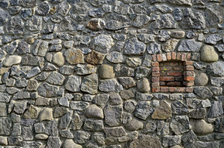 Antique wall of granite stones with a window 免版税图像
