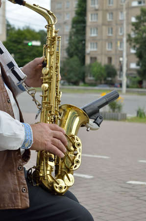 Old musician playing saxophone on empty street