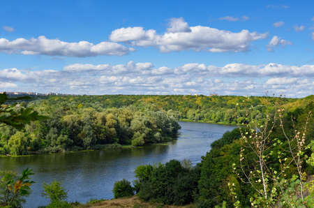 River among the wooded coasts against the blue sky